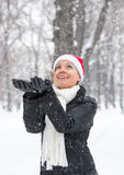 Woman catches hands snowflakes for Christmas Royalty Free Stock Image