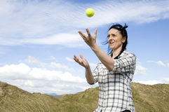 Woman catching ball. Woman catching tennis ball in sand dunes stock photography
