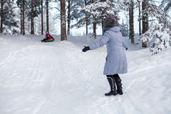 Woman catching child tubing on downhill in winter wood Royalty Free Stock Image