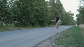 Woman catching the hitch-hiking car on the road stock video footage
