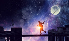 Woman catching moon . Mixed media Stock Images