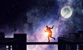 Woman catching moon . Mixed media Royalty Free Stock Images