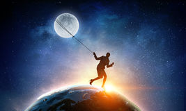 Woman catching moon Stock Photo