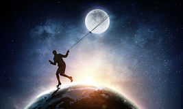 Woman catching moon Royalty Free Stock Photography
