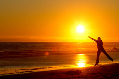 Woman catching sunset on beach. Silhouetted girl reaching out to touch colorful sunset on beach with sea in background Royalty Free Stock Photo