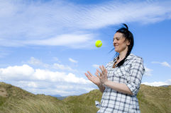 Woman catching tennis ball. In sand dunes with blue sky stock image
