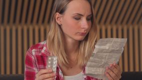 Woman caucasian woman with medicine and reading drug prescription. Tilt shot stock footage