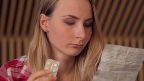 Woman caucasian woman with medicine and reading drug prescription. Tilt shot stock video