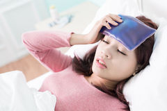 Woman caught Cold and fever. Sick Woman caught Cold and fever or Headache and lying on bed at home. asian female Stock Photography