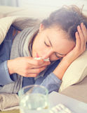 Woman caught cold. Sneezing into tissue stock images