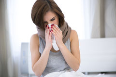 Woman caught cold. sneezing into tissue