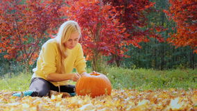 Woman causes pattern on the pumpkin. Preparing for Halloween. Young woman carves a pumpkin. Sitting in the yard in the background of yellowing and orange trees stock video footage
