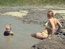 Woman cautiously descends into a mud volcano to medical procedures. Mother gently bathing my daughter in the mud. Treatment non-traditional methods Stock Photo