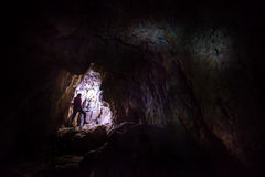 Woman caver spelunker exploring the cave Stock Photography