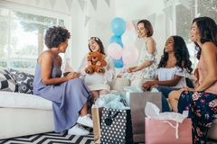 Woman celebrating baby shower with friends. Pregnant women celebrating baby shower party with friends. Pregnant women receiving gifts from friends Stock Image
