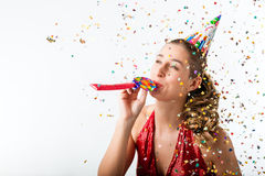 Woman celebrating birthday with streamer and party hat. Woman celebrating birthday and hooting with horn at a shower of confetti Royalty Free Stock Photos