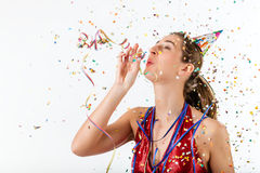 Woman celebrating birthday with streamer and party hat. Woman celebrating birthday and hooting with horn at a shower of confetti royalty free stock photography
