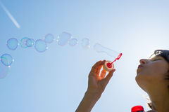 Free Woman Celebrating Blowing A Stream Of Bubbles Stock Photo - 53510700