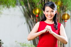 Woman celebrating Chinese new year. Traditional greeting, wearing red dress