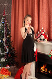 Woman celebrating christmas, smiling woman in evening dress with glass of sparkling champagne Royalty Free Stock Image