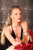 Woman celebrating christmas, smiling woman in evening dress with glass of sparkling champagne Royalty Free Stock Images