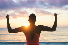 Woman celebrating fitness beach summer workout success. Fitness woman celebrating fitness workout success and motivation towards the sea and sunset Royalty Free Stock Images