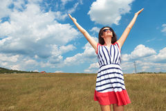 Woman celebrating freedom in the middle of a field. Happy young woman celebrating freedom in the middle of a field, holding her hands up stock photos