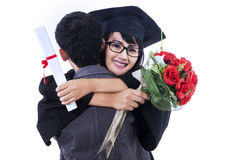 Woman celebrating graduation day with her boyfriend. Happy women is hugging boyfriend on graduation day. isolated on white background Stock Image
