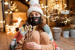 Woman celebrating New Year holidays alone. Portrait of a sad woman in facial mask celebrating alone New Year holidays. Holding candles 2021 with a hope that the