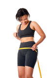 Woman celebrating successful weightloss. Beautiful happy toned woman weight conscious measuring her size shape around waist hips, celebrating her successful Royalty Free Stock Images