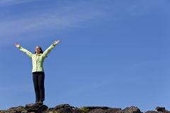 Woman Celebrating On Top Of A Mountain Stock Photo