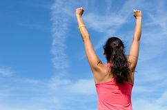 Woman celebrating win. Woman from behind with arms raised expressing success towards sky on a sunny summer day Royalty Free Stock Images