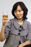 Woman Celebrating With Wine. Young beautiful asian business woman celebrating her success with wine and sit on the table Stock Photos