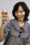 Woman Celebrating With Wine. Young beautiful asian business woman celebrating her success with wine and sit on the table Royalty Free Stock Photo