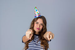 Woman in celebration cap holding pointing fingers in front of he Royalty Free Stock Photography