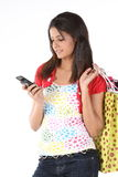 Woman with cell holding lots of shopping bags Stock Photography