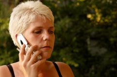 Woman On Cell Phone. Young woman with short blond hair talking on a cell phone Stock Photo