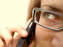 Woman with Cell Phone. Partial face view of attractive woman in eyeglasses and holding cell or mobile phone to ear royalty free stock photo