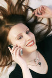 Woman with cell phone. A beautiful young woman lying on bad and using a cell phone Royalty Free Stock Photos