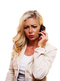 Woman on Cell phone. A attractive blond woman is talking on her cell phone with a serious look on her face royalty free stock image