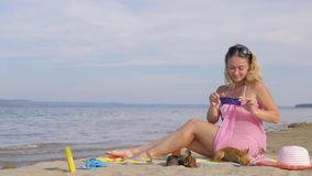 Woman with cell phone on the beach. She rewrites by phone, looks at photos, makes selfies. The girl is taking pictures of the sea on the phone. Two of her stock video