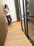 Woman On Cell Phone At Bottom Of Stairs Stock Images