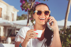 Woman with cell phone enjoying coffee at sidewalk cafe Royalty Free Stock Photo