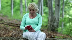Woman with cell phone in the forest stock video
