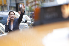 Woman on Cell Phone Hailing a Yellow Taxi Cab Stock Image
