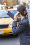 Woman on Cell Phone Hailing a Yellow Taxi Cab Royalty Free Stock Photography