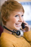 Woman on cell phone with headphones. Young smiling woman talking on cell phone with headphones around her neck Royalty Free Stock Photos