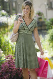 Woman with cell phone and shopping bags Stock Photos