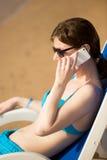 Woman on cell phone on sun deckchair stock image
