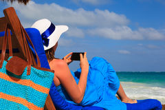Woman with cell phone on tropical beach Stock Photos